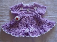 This is a new beautiful purples and white colored crochet girl dress and headband set is for size 0 - 3 months.On the beautiful dress there are shiny flowers and beads. It is knitted by bernat baby super fine acrylic yarn. It has nice designs. Behind it there are 3 buttons.