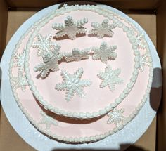 White snowflakes on a pale pink two tier cake