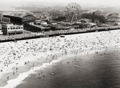 Sunbathers on the beach at Coney Island in in 1953, with the ferris whell and Cyclone roller coaster in the background.