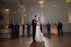 Bride and groom's first dance. I love how the wedding party is in full view behind them. What a beautiful shot!