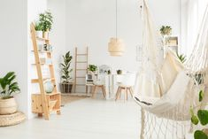 Picture of White macrame hammock in spacious dining room interior with decorations on wooden ladder and rattan lamp above the table stock photo, images and stock photography. Nasa, Home Office, Interior Decorating, Interior Design, Air Purifier, Shabby Chic Decor, Room Interior, Indoor Plants, Whitening