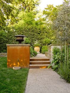 """""""Focal points including the small, stone bowl, a fountain atop the steel wall, and a Venetian-style urn at the end of the path draw the eye through the landscape."""" Gravel Path, Scot Eckley Inc. Seattle, WA"""