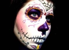 YouTube user goldiestarling teaches you how to apply a sugar skull from purple crush makeup look. Use a white eyeliner to create the sockets of the skull, then go around the nose area. Color the whole face using a creamy white pencil and add red blush on the cheeks. Use a creamy purple color to fill in the sockets and the tip of the nose. Draw small flower petals on the edges of each socket. Use a black color to draw a spider web on the forehead. Then draw bone like structures near the mouth…