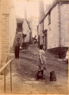 A photograph of a cobbled pathway leading from a street in Newlyn. On the right are a flight of granite steps leading to an upstairs door. A young girl stands in the centre of the street looking elsewherem with a milk churn on the floor by her side.A man, possibly a fisherman, stands to the left looking at the camera, wearing a bowler hat and having a thick beard and moustache. A small girl, half obscured, stands to the right 1880-1890.  Penlee House Gallery and Museum Penzance Cornwall UK