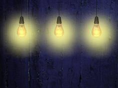 three yellow light bulbs against indigo wooden boards