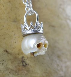 White pearl with cream tones, carved into skull wearing a sterling silver crown and on a sterling silver chain. Pearl is 8 mm. Sterling silver