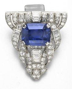 AN ART DECO SAPPHIRE AND DIAMOND CLIP BROOCH   Set with a cushion-cut sapphire, weighing approximately 16.81 carats, within an openwork baguette and circular-cut diamond geometric surround, mounted in platinum, circa 1925
