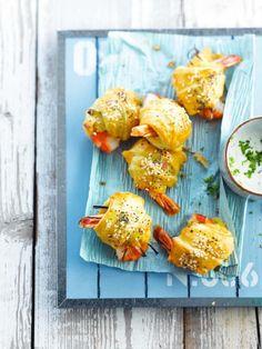 Bereiden:Verwarm de oven voor op 180 graden.Leg de plakjes bladerdeeg (liefst vierkante blaadjes bladerdeeg van 10 op 10 cm) op een met bakpapier beklede bakplaat. Snij het bladerdeeg en de plakjes kaas in lange reepjes van 3 cm breed.Versnijd de lente-ui in julienne van 8 cm lang.Beleg de reepjes bladerdeeg met kaas, reepjes lente-ui en een scampi. Kruid met peper en zout. Rol op en druk het uiteinde van de bladerdeeg goed aan.