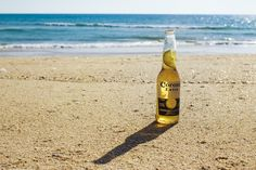 A bottle of beer with a lime slice on coarse sand by the sea