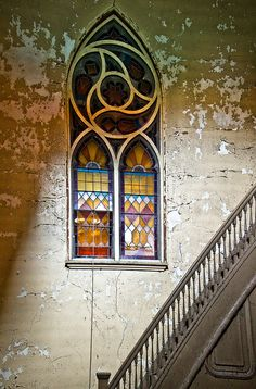 Stained Glass Stairs - Jonathon Much, An untouched stained glass window, surrounded by peeling paint on the far wall of a staircase shows how beautiful the Transfiguration church in Buffalo, NY must have been before it was abandonded.