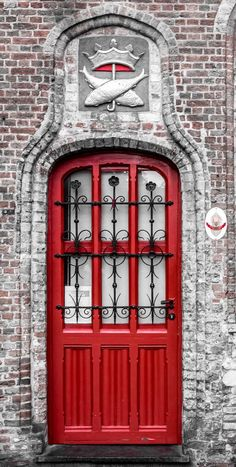 This red door from Belgium is a great example of how the right trim and accents can make a great door fantastic.  This arsied panel door has wrought iron grills, but what takes it over the top is the masonry carving above and around the door.  We install great #doors in the Minneapolis MN area - you can accent them with your personal touches. http://www.replacementwindowsmpls.com