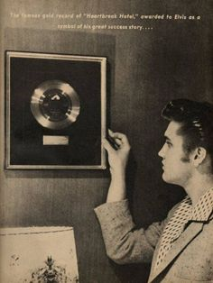 """Elvis with his first gold record for his first million-seller """"Heartbreak Hotel"""" hanging on the wall in the living room of his house at 1034 Audubon Drive in Memphis, TN on Tuesday, June 19, 1956. """"Heartbreak Hotel"""" was recorded on January 10, 1956 and released by Elvis's new record label RCA Victor on January 27, 1956. The song entered the Billboard pop chart at number 68 on March 3, 1956, became a million-seller in April and finally reached number 1 on May 5, 1956."""