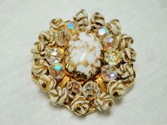 This vintage brooch is a show stopper. It is made up of a large center milk glass stone with gold streaks going through it. It is then surrounded by ten aurora borealis gla...