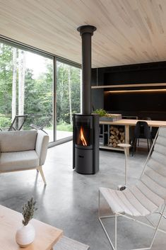 A rotating wood stove in the center of the open-concept living and dining area provides 360-degree access to the fire. #dwell #canada #prefabhomes #moderncabins Prefab Cabins, Prefab Homes, Polished Concrete Flooring, White Mosaic Tiles, House Shutters, Compact House, Hotel Concept, Sliding Panels, Interior Exterior