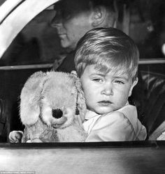 July 20, 2016 - Time for bed: Prince Charles, aged 20 months, cuddles his toy dog and looks sleepily at the crowds through the car window as he is driven home. ~ Photo by INTERNATIONAL NEWS PHOTO.
