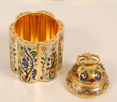 A magnificent and exceptionly rare Russian silver gilt and shaded champleve enamel tea caddy by Ivan Khlebnikov, Moscow, 1896-1908. The six, cylindrical lobed sides beautifully decorated in various alternating multi-color scrolling floral and foliate motifs against a matte gilt ground, the double-domed lid similarly worked with floral designs and paisley motifs between stylized pineapples. From John Atzbach. (third view)