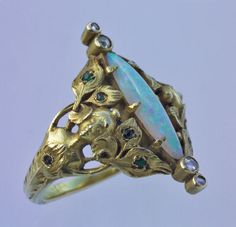 ART NOUVEAU  Peacock Maiden Ring   Gold Opal Emerald Diamond  H: 2.5 cm (0.98 in) W: 2 cm (0.79 in)  Marks: Indistinct maker's mark  French, c.1900  Ring Case  Opal 1.75 cts approx