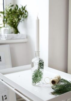 Beautifully simple Nordic Christmas ideas using fir tree cuttings in bottles of water as candlesticks.