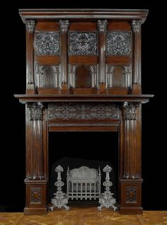 Antique Jacobean English Renaissance manner Fireplace carved in Oak. The overmantel with four fluted columns and ornate florally decorated capitals enclosing two rows of three panels, the upper with intricate carved floral designs the lower with Gothic niches, carved with Celtic strapwork. English, part 17th century, rebuilt in the 19th century with matching elements.