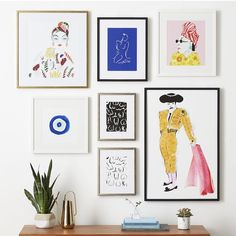 Gretchen says: Minimalists live here! Space, where the eye can rest is a minimalists calling card. Notice all the white matts, white wall and space left exposed on top of the chest. The art to the left is hung higher allowing space for the tall plant,balancing the entire composition. Blue and pinks with pops of black & yellow is the palet.
