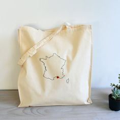 A custom tote bag embroidered with the outline of the France map. The France and Corsica map makes a perfect personalised map gift.  Small love heart buttons can be sewn on to mark your special place or places.  A cotton tote bag with long handles measuring approximately 38 cm by 43 cm (15 inch by 17 inch). The handles are approximately 26 inch(65cm) long. The gusset is 4 inch wide. The bag can be hand washed. A good size for a gym bag, book bag or many other uses.  Available in a choice of…