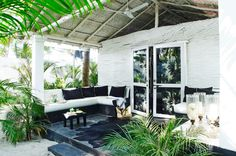 A porch with built-in seating functions as an alternate living room.