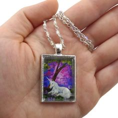 """Do you need blessings from a unicorn? Capture the magical powers of """"Beauty"""", a stunning white creature relaxing beneath a sturdy tree in a forest soaked with the purple light of dusk.  Fantasy Art Pendants by KK Swann allow you to feed your whimsy wherever you go. Attract good luck and health with this necklace featuring Drakey Art's original painting """"Beauty"""". Customizable to fit your personal style, choose your favorite metal from silver or gunmetal; and select your preferred shape (for…"""