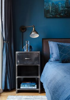 Emery drapes by Pottery Barn; Pewter sconce by RH Baby&Child; Distressed steel nightstands by Boltz Furniture; Isaac charcoal queen bed by Crate&Barrel; Retro collection rug by Safavieh; Real Simple coverlet by BedBath&Beyond