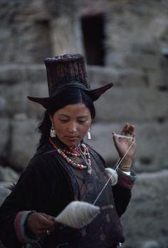 Ladakhi woman spins sheep's wool on a twirling distaff.  Location:Ladakh District, India.