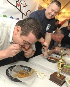 "With the coveted trophy in reach, #FallRiver Police Department anchorman Mike Perreira presses on to win, despite the elbow in the ribs and pleas to ""slow down... take your time.... chew"" from his opponent, New Bedford Police Sgt. Dean Fredericks at the second annual Wing Eating Contest."