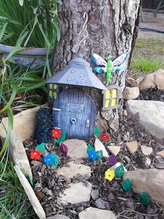 """A work in progress, this is the Fairie Garden I've started in my yard.  The door and windows were purchased at a yard sale and the door has a sign on it that says """"Faeries Sleeping"""".  I took a metal outdoor candle holder that was all rusted out apart and painted the flowers, leaves and made the top part of it an awning over the door, painted it and the flower embellishments.  The dragonfly used to be a flower pot hanging ornament."""