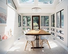 Dining Room Photo - A wood dining table surrounded by white chairs