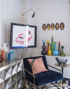 The Jonathan Adler Goldfinger Chair tucked away in a colorful corner of his NYC den. The Talitha Credenza adds a touch of graphic glamour paired with fun JA pottery and pop decanters.