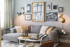 Living room features gray walls adorned with a black,white and gold gallery wall over a modern gray sofa with chaise lounge layered with Mongolian wool and gold silk pillows along with a black and white striped throw.The gray sectional is flanked by a pair of black and gold end tables, illuminated by a brass pivot floor lamp and modern brass table lamp alongside a West Elm Marble Oval Coffee Table adorned with a gold tray, stacked books and black candlesticks atop a gray and white chevron…