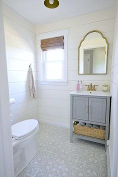 A stunning farmhouse style powder room renovation that includes gray and gold tones, shiplap walls as well as beautiful cement tile floors.