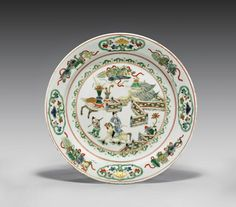 """KANGXI PERIOD FAMILLE VERTE PORCELAIN DISH the circular plate with figural design of an equestrian in a courtyard with attendant, a running fence and a table of offerings, the border with scholarly emblems alternating with foliate reserves; gilt accents, the underside with floral sprays; D: 9"""""""