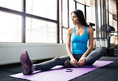 Woman sitting on yoga mat. http://photodune.net/item/woman-sitting-on-yoga-mat/11063578