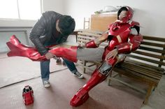 Cheng Chen (L), a 27-year-old worker at a state-owned enterprise, helps his nephew to put on his home-made Iron Man armour in Xuzhou, Jiangsu province, China, April 13, 2015. It cost Cheng about 500 yuan ($81 USD) to make the armour, which weighs about 4 kilograms, with plastic boards and LED lights, local media reported. REUTERS/Stringer