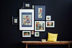 Imagem com uma galeria de molduras numa parede, numa combinação de tamanhos, com um banco de madeira e uma almofada amarela.