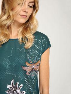 """Damska bluzka Top Secret z kolekcji jesień-zima 2016. <br><br>Damska bluzka bez rękawów w kolorze ciemnozielonym z kwiatowym printem. Oversizowy krój sprawdzi się w casualowych stylizacjach zarówno w zestawieniu z jeansami, jak i spódnicą. Bluzka dostępna w kolorze ciemnozielonym (SBW0301CZ).<br><br><span style=\""""front-style:italic\""""> Modelka ma 179 cm wzrostu i prezentuje rozmiar 36."""