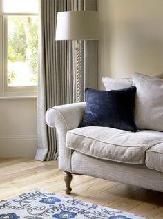 Classical sofa in soft grey linen with blue velvet cushion and Neisha Crosland rug on oak wooden floor.