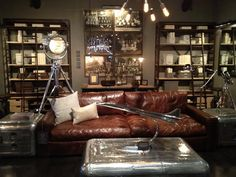 Restoration Hardware aviation sculpture, aluminum trunk coffee and side tables, large chrome tripod lamp, vintage prints surrounded by large library bookcases - not a fan of this sofa because their Kensington sofa looks so much more masculine and stylish