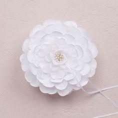 Op zoek naar een originele manier om jullie ringen naar voor te laten brengen? Dan is dit witte ringkussentje in de vorm van een bloem zéker jullie ding. Achteraan het ringkussentje is een handig lusje voorzien waar het bruidsmeisje of jongen hun hand kan doorsteken. De ringen worden netjes op hun plaats gehouden door de lintjes.