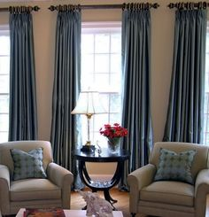 Blue drapes with neutral chairs/floor. BBB has nice grommeted drapes (Trilogy in Slate Blue, same style Kim has in her bedroom) or get the ring top style that Aunt Chris has in her living from (I think her rod/rings are from Pottery Barn).
