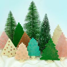 <p>Designed By Karen Benvenuti</p> <p>Create a frosty winter forest of sparkling evergreens when you add glitter to your Perler beads before fusing. These trees make a great holiday decoration for a mantel or table, and they're quick and easy to do! </p>