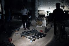 Syrian rebel fighters stand around a cache of homemade missiles which they say they use on forces loyal to president Bashar al-Assad in Aleppo province August 21, 2012. The rebels said they retrieve explosive materials from government shells which failed to explode.