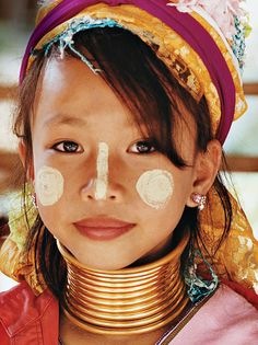 """A young Padaung girl at Baan Tong Luang, a """"cultural preservation"""" village outside Chiang Mai where four hill tribes sell crafts and demonstrate skills. Padaung females are recognized by their practice of elongating their necks with brass coils"""