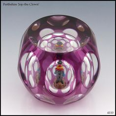 Perthshire Paperweights Limited Edition, 'Jojo the Clown'. The lampwork clown stands inside a hollow blown, overlaid and facetted glass paperweight. www.pwts.co.uk