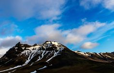Mountain and blue sky - Snowy Icelandic mountains with dramatic cloudy sky - amazingly peaceful landscape of Iceland.