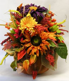 """A foam pumpkin filled with sunflowers, leaves and grasses makes a beautiful centerpiece or fall accent. The colors reflect the season with purple, deep reds, gold, yellow and orange. Measures 19""""H X 1"""